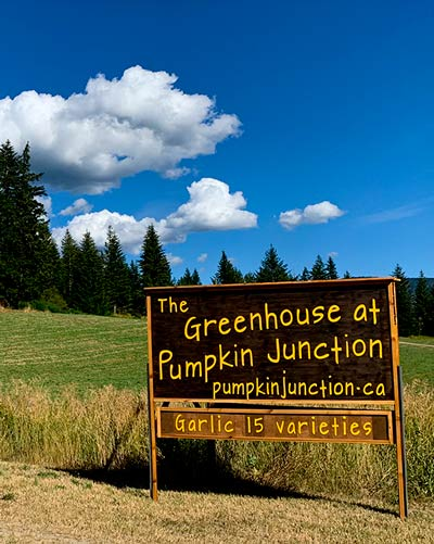 The Greenhouse at Pumpkin Junction sign in front of blue sky.